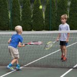 Two young male Camp Dunnabeck campers volley tennis ball close to the net.