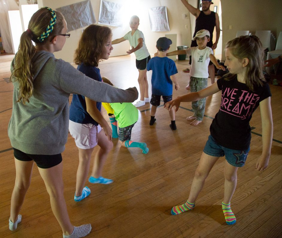 Camp dunnabeck Theater group does improve skit, campers move in small group, arms up like dancing