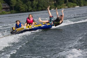 Three Camp Dunnabeck campers ride over the crest of a wave on a water tube, one boy is falling off the edge of the raft