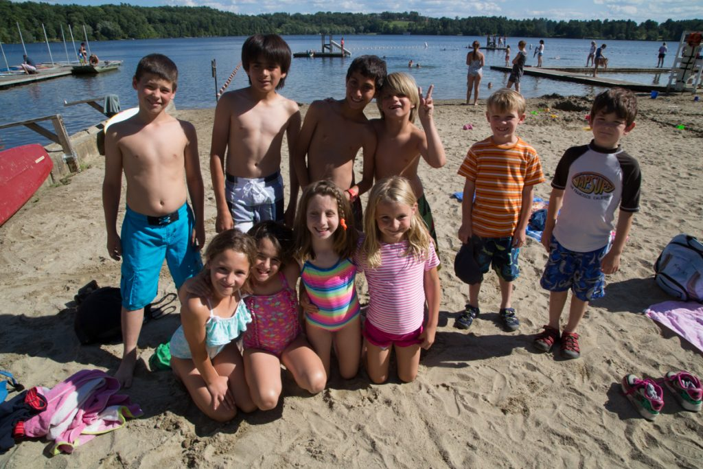Group of elementary-aged campers pose lakeside in swim gear on sand.