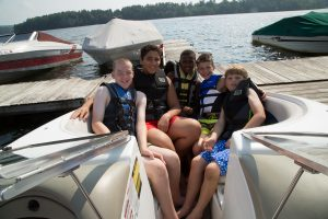6 Camp Dunnabeck campers sit in a tight group in the back of a motor boat at the dock