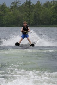 Camp Dunnabeck camper on water skis, front angle photograph