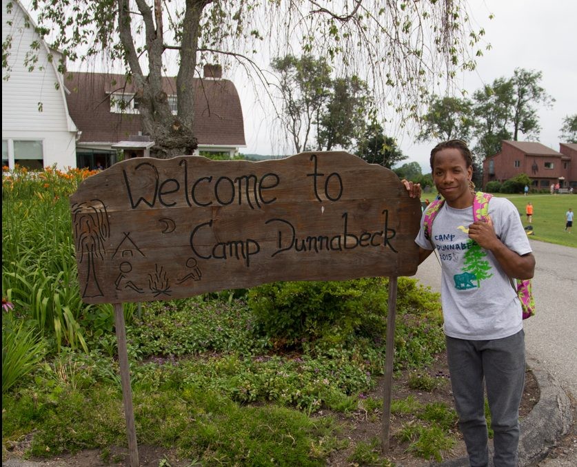 "Wooden sign says, ""Welcome to Camp Dunnabeck"", teen boy stands to the right of the sign near garden."