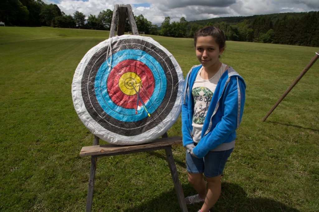 Female Camp Dunnabeck camper stands next to an archery target with her arrows stuck near the center ring.