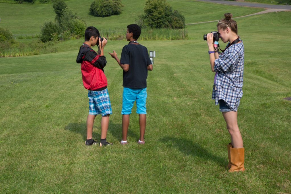 Three camp dunnabeck campers stand in a field taking photographs.