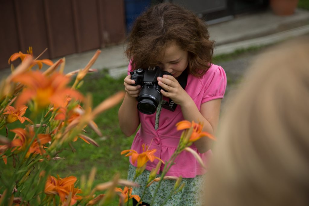Camp Dunnabeck girl takes photograph of tiger lilies.