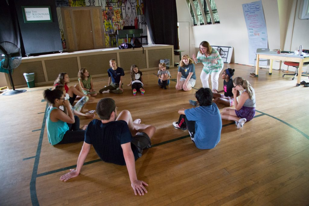 Theater group sits in a circle, Camp Dunnabeck campers listen to instructor standing to right of circle