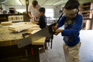 Camp Dunnabeck boy cuts a board with a saw inside a woodshop