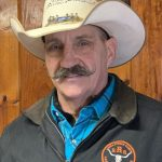 Inside portrait of male stables director with cowboy hat, handlebar mustache, leather jacket and blue plaid.