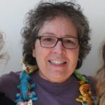 Inside portrait of female tutor with short salt and pepper hair, glasses, purple shirt, multi-colored scarf.