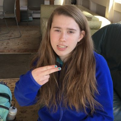 "Teen girl in blue sweater make a ""p"" using American Sign Language."