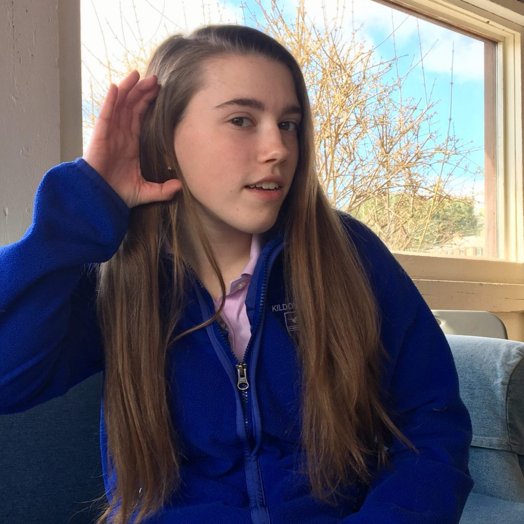 Teen girl in blue top demonstrates American Sign Language.