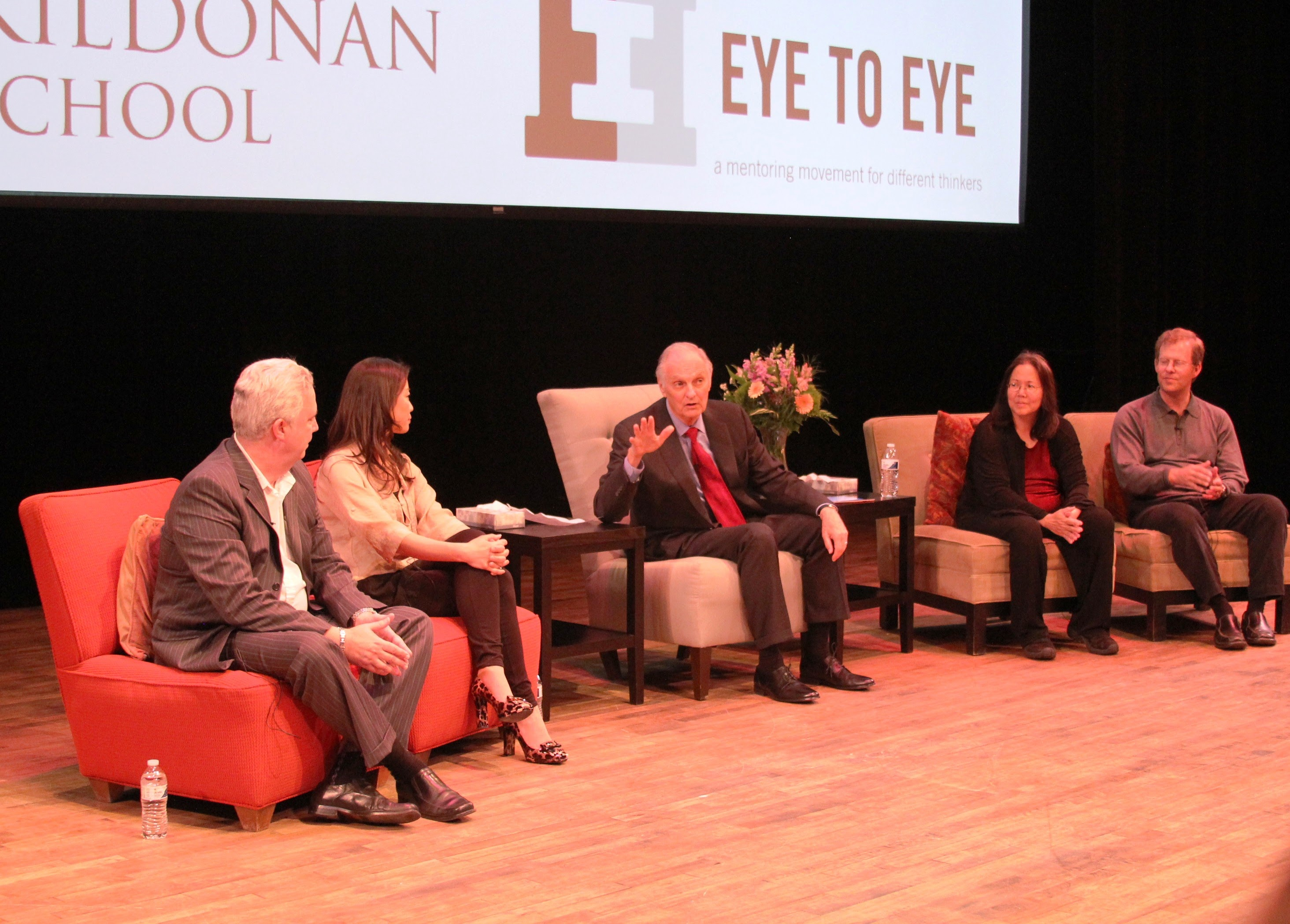 Four panelists sit with Alan Alda in front of Kildonan School and Eye to Eye banners.