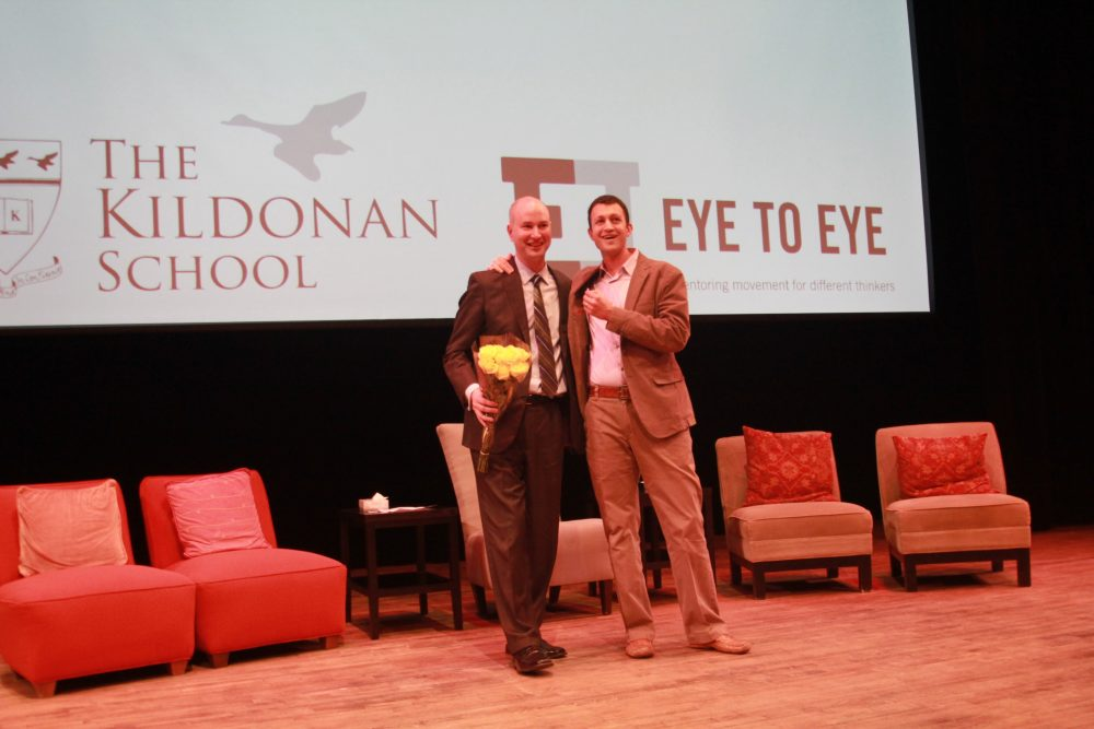 Two men stand together on a stage with Kildonan and Eye to Eye banner in background.